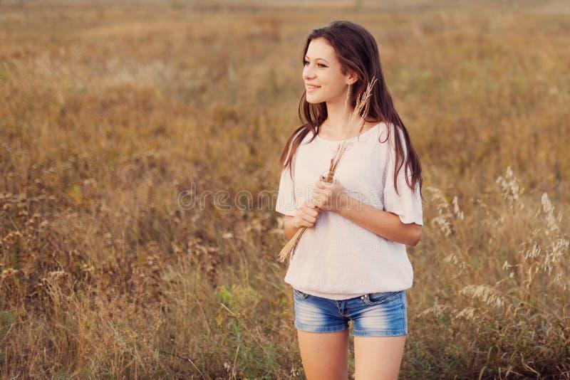 Het jonge meisje met lang bruin haar houdt een bundel van in hand oren stock afbeeldingen