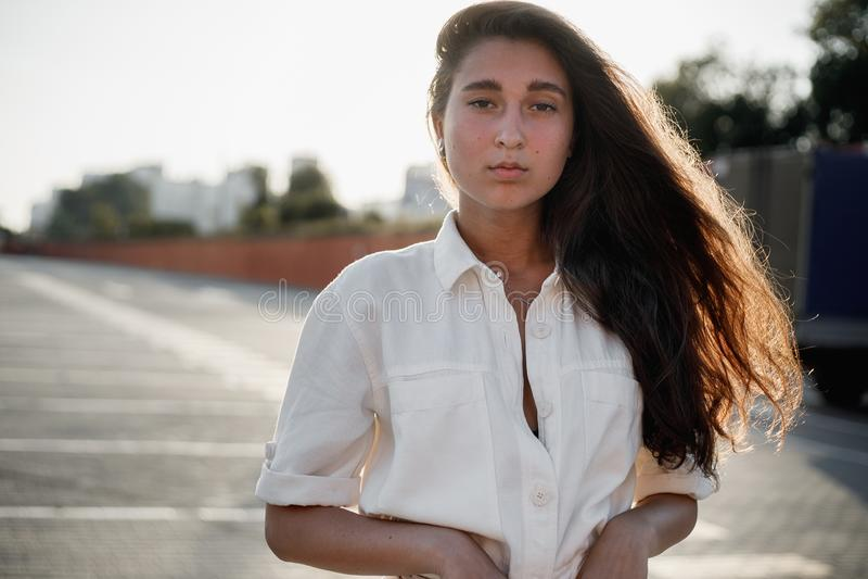 Het jonge meisje met lang donker haar gekleed in wit overhemd bevindt zich in de straat in de heldere zonneschijn stock afbeeldingen