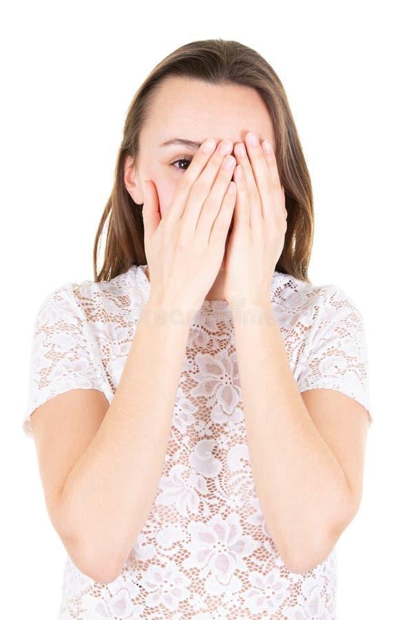 Het jonge meisje met lang haar behandelt zijn gezicht met zijn handen stock foto