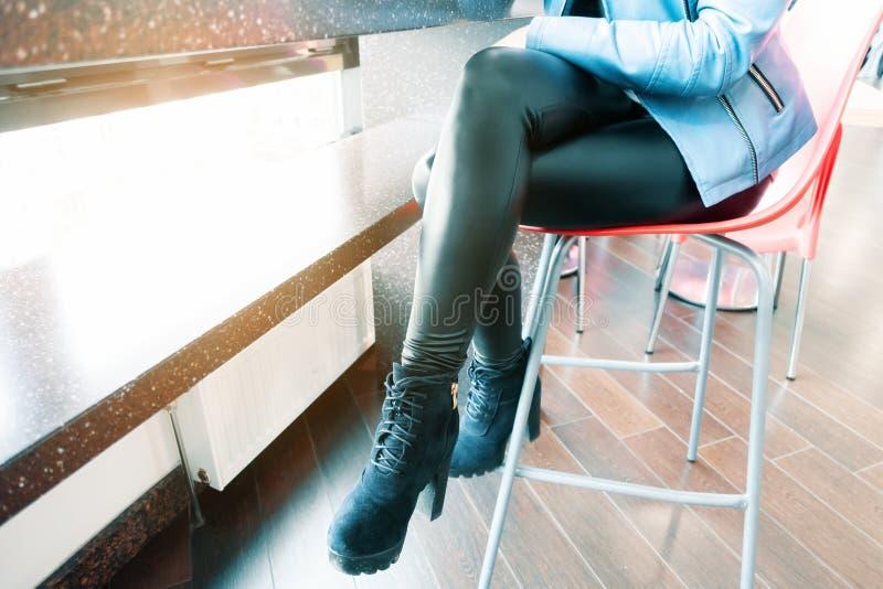 Het jonge meisje met mooie benen zit op een stoel in een koffie achter de bar royalty-vrije stock foto's