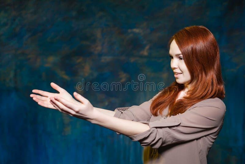 Het jonge meisje met rood haar houdt handen stand stock fotografie