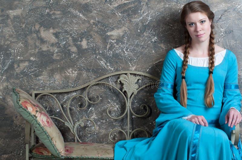 Het jonge meisje in middeleeuwse kleding zit op een banquette stock foto