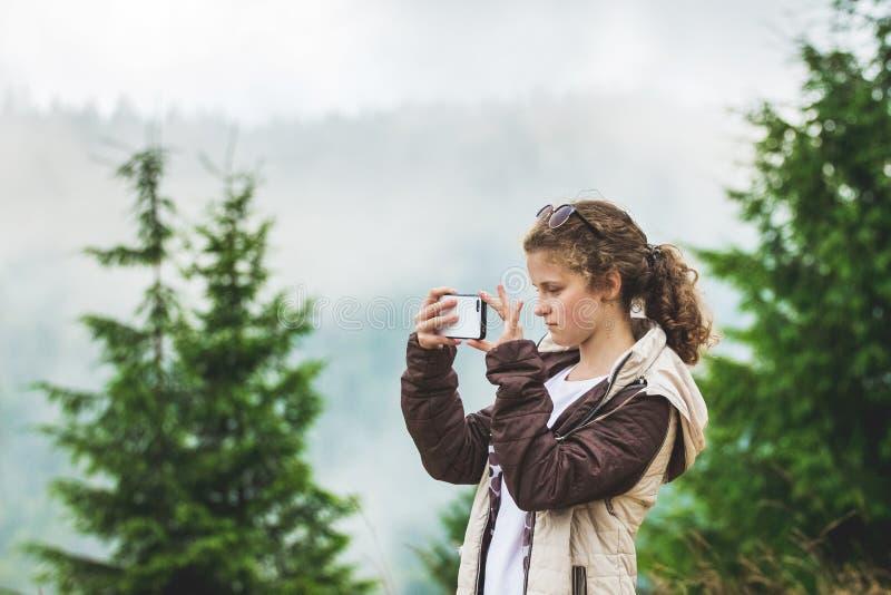 Het jonge meisje neemt een beeld van een berg landscape_ stock afbeelding