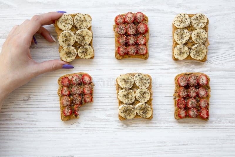 Het jonge meisje neemt veganisttoost met vruchten, zaden, pindakaas over witte houten achtergrond, hoogste mening Het op dieet zi stock foto