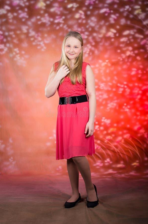 Het jonge meisje in rode kleding stelt in studio stock foto's