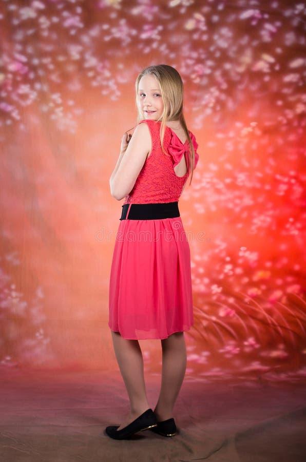Het jonge meisje in rode kleding stelt in studio stock foto
