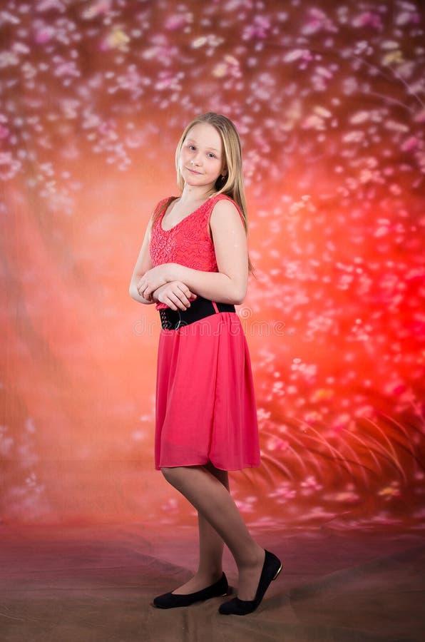 Het jonge meisje in rode kleding stelt in studio royalty-vrije stock afbeelding