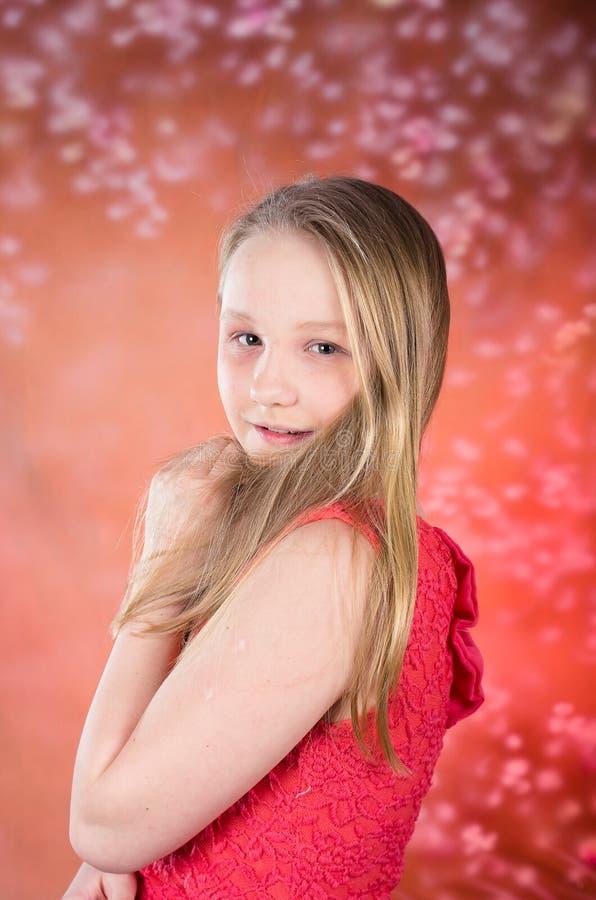 Het jonge meisje in rode kleding stelt in studio stock afbeelding