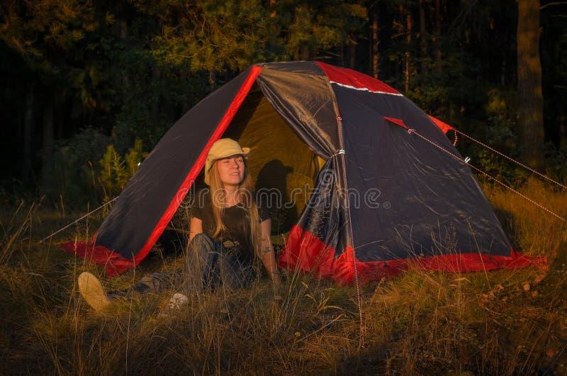 Het jonge meisje rust dichtbij het kamp royalty-vrije stock afbeeldingen