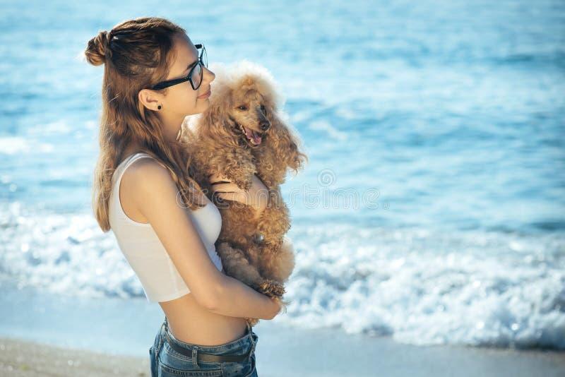 Het jonge meisje rust met een hond op het overzees stock foto's