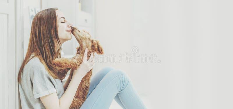 Het jonge meisje rust thuis met een hond op de vloer royalty-vrije stock afbeelding