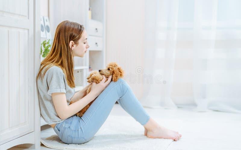 Het jonge meisje rust thuis met een hond op de vloer stock fotografie