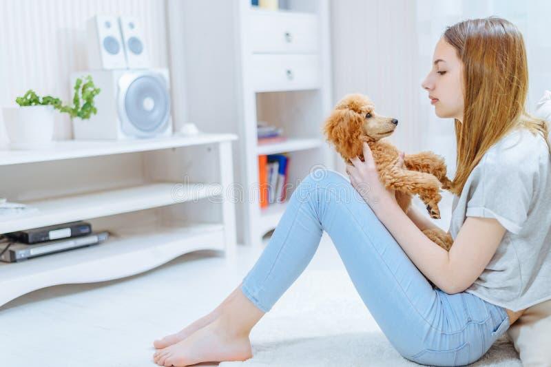 Het jonge meisje rust thuis met een hond op de vloer royalty-vrije stock foto's