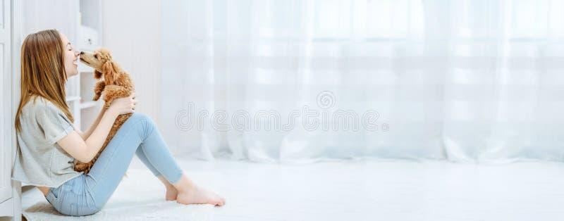 Het jonge meisje rust thuis met een hond op de vloer stock afbeeldingen