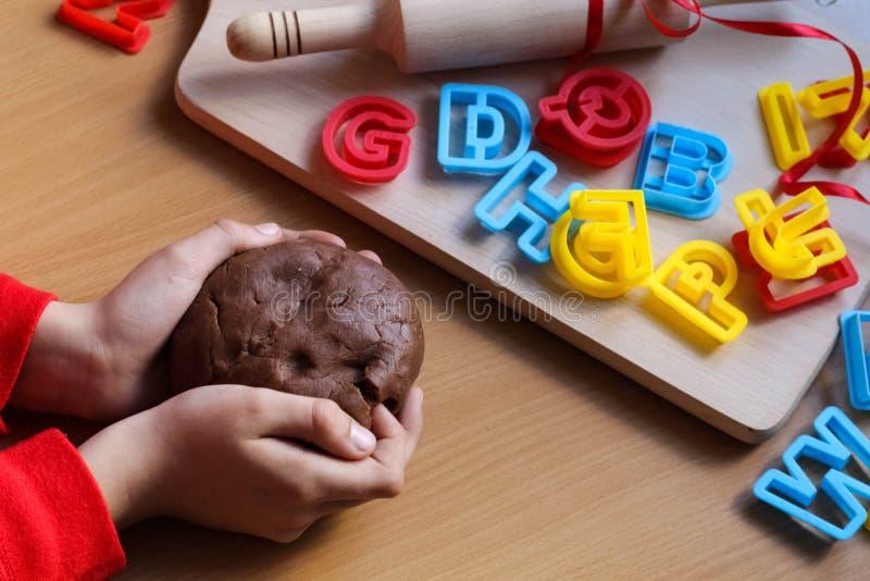 Het jonge meisje ` s overhandigt het kneden deeg Kokende traditionele Pasen-koekjes Pasen-voedselconcept stock afbeelding