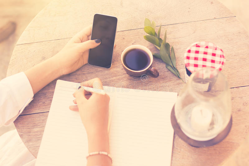 Het jonge meisje schrijft in een notitieboekje met celtelefoon en kop van coffe stock foto