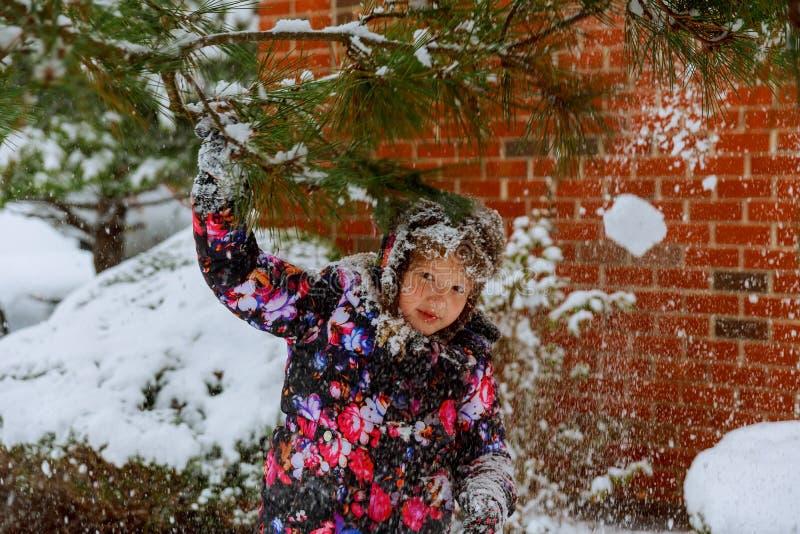Het jonge meisje speelt met sneeuw Gelukkige het Meisjes Blazende Sneeuw van de schoonheidswinter in ijzig de winterpark of in op stock afbeeldingen
