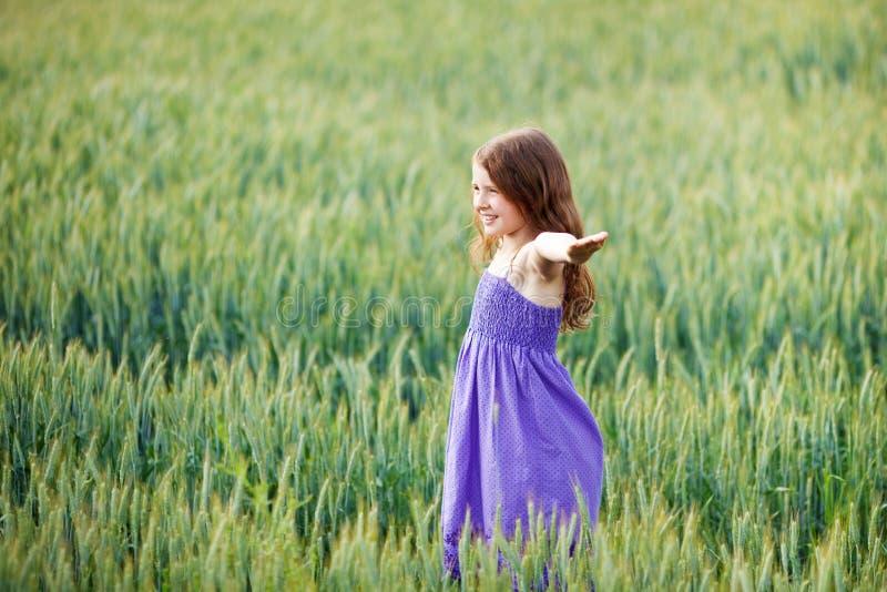 Het jonge meisje spelen in een wheatfield stock foto