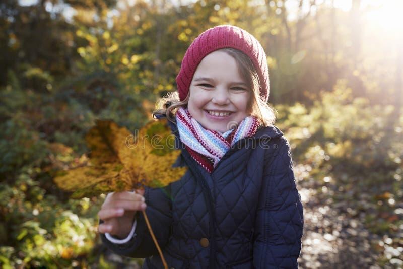 Het jonge Meisje Spelen met Bladeren op Gang in Autumn Countryside stock fotografie