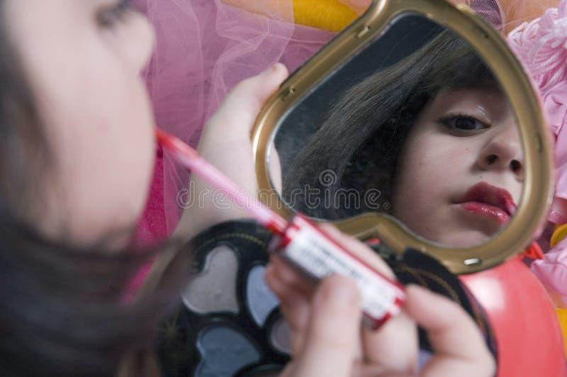 Het jonge meisje spelen met haar maakt omhoog uitrusting stock foto
