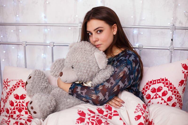 Het jonge meisje spelen met teddybeer in bed stock afbeelding