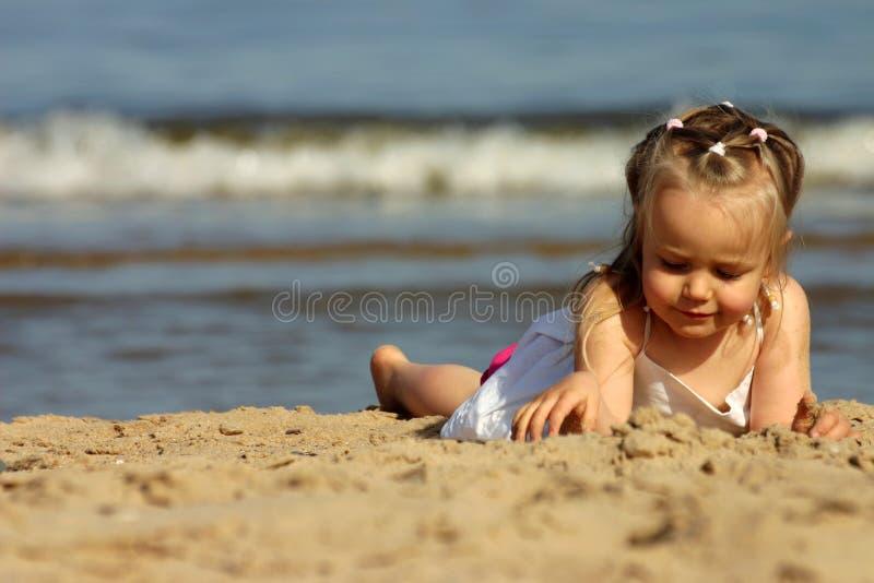 Het jonge meisje spelen met zand o stock foto