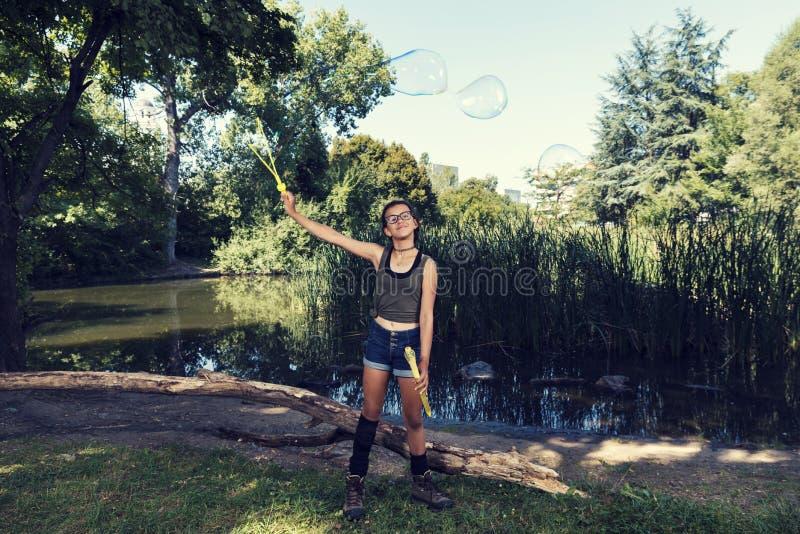 Het jonge meisje spelen met zeepballons in een de Zomertijd van het stadspark royalty-vrije stock foto