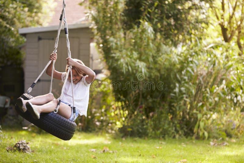 Het jonge Meisje Spelen op Bandschommeling in Tuin royalty-vrije stock afbeeldingen