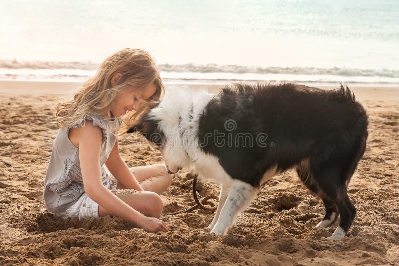 Het jonge meisje spelen in zand op strand met border collie-hond stock foto's