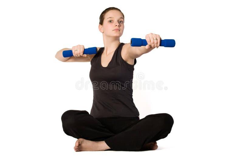 Het jonge meisje is sportief met gewichten stock afbeeldingen