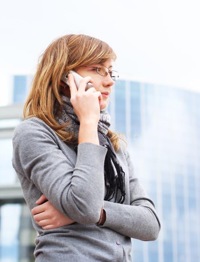 Het jonge meisje spreekt door mobiele telefoon. zaken stock foto