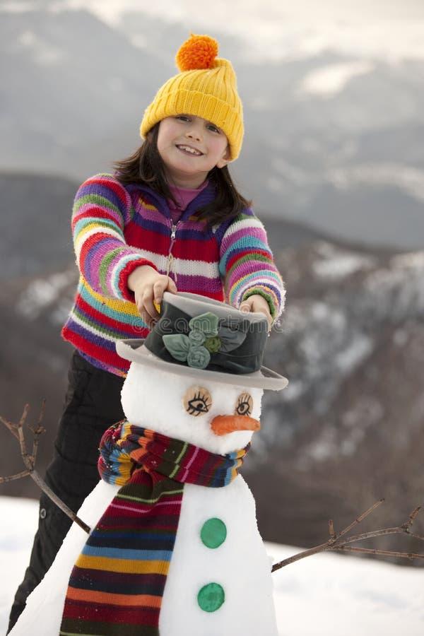 Het jonge meisje stellen met haar sneeuwman stock fotografie