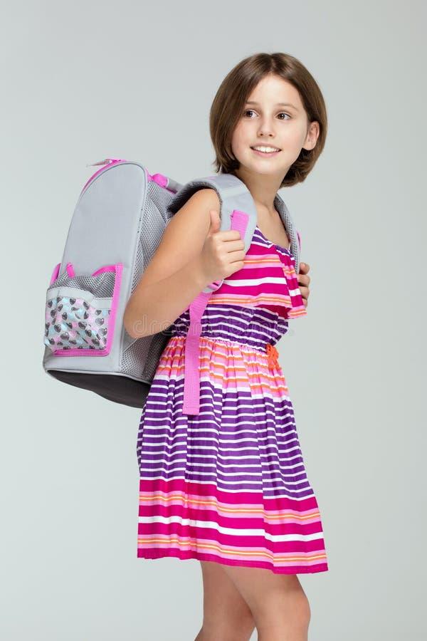 Het jonge meisje stellen met schoolrugzak stock foto's