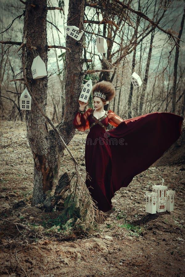 Het jonge meisje stelt in een rode kleding met creatief kapsel royalty-vrije stock foto's