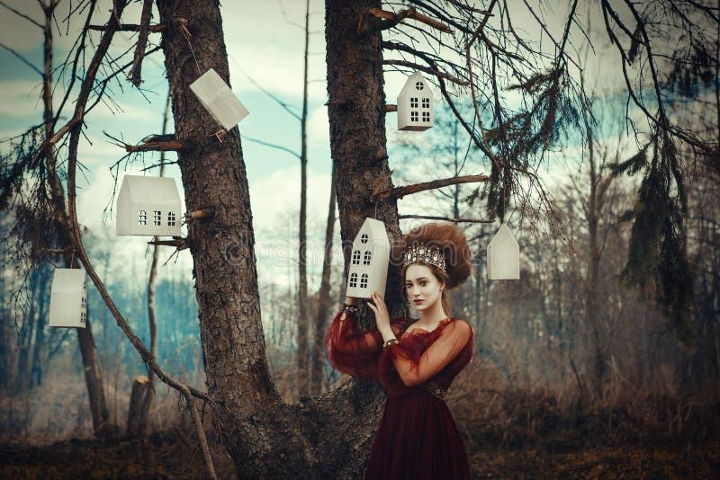 Het jonge meisje stelt in een rode kleding met creatief kapsel royalty-vrije stock foto