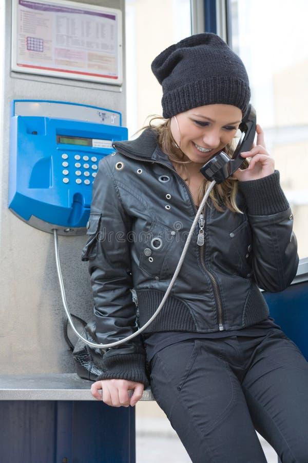 Het jonge meisje in telefooncel royalty-vrije stock afbeelding