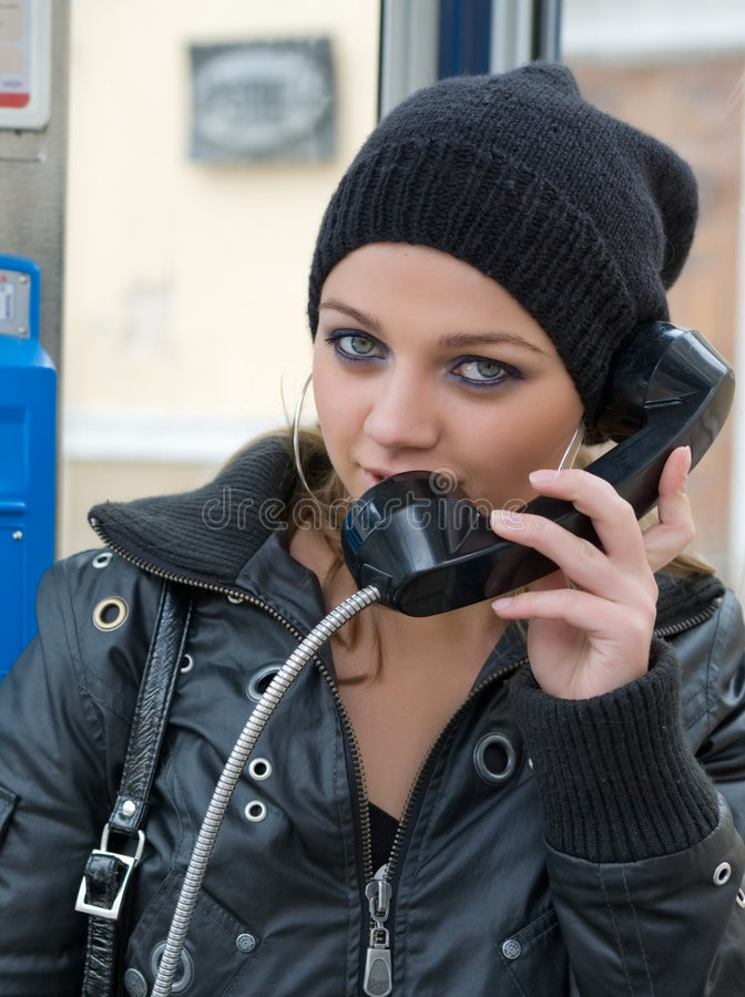 Het jonge meisje in telefooncel royalty-vrije stock afbeeldingen