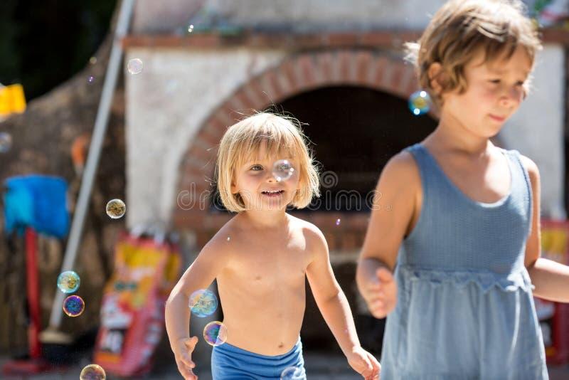 Het jonge meisje van het blondekind met vriend of zuster het spelen met zeepbels Warm zonsonderganglicht De familiezomer trave royalty-vrije stock fotografie