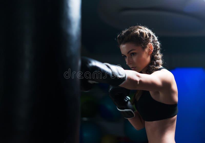 Het jonge meisje van de vechtersbokser in opleiding met zware ponsenzak royalty-vrije stock foto