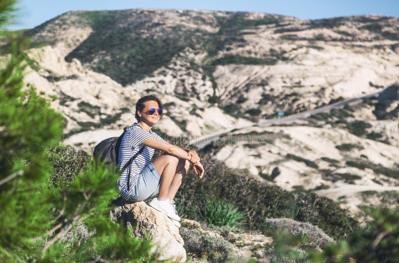 Het jonge meisje van de vrouwenreis met rugzak zit achtergrond van mountai stock fotografie