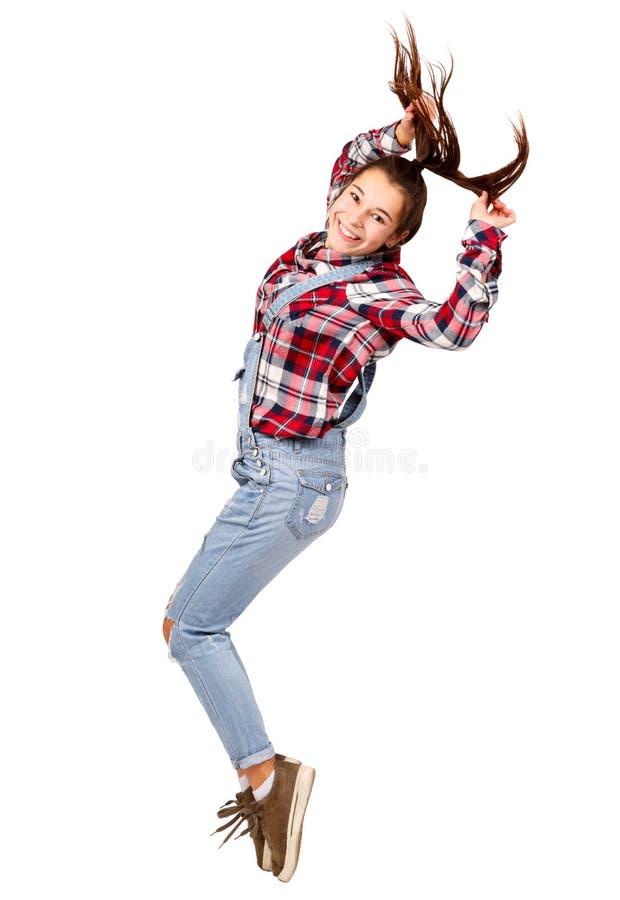 Het jonge meisje, van gemiddelde lengte, in profiel bevindt zich op tenen, dansen, geïsoleerd op witte achtergrond stock foto's
