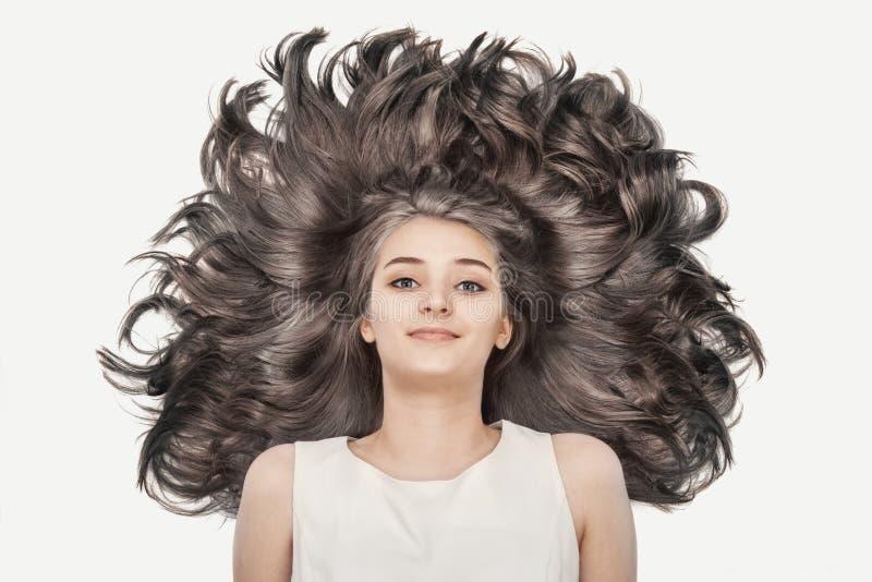Het jonge meisje van Nice met luxueus blond haar op een witte achtergrond stock afbeeldingen