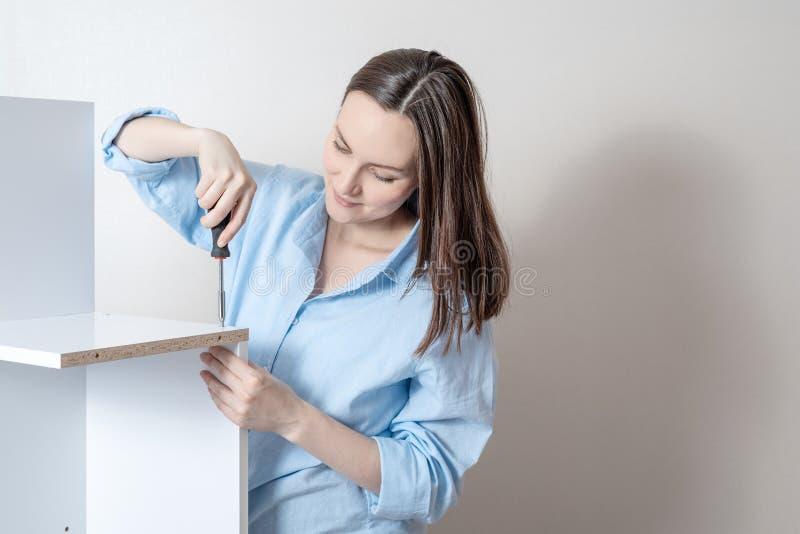 Het jonge meisje verzamelt meubilair met een schroevedraaier, exemplaarruimte stock afbeelding