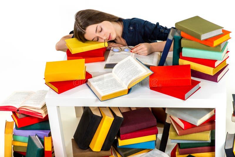 Het jonge meisje viel in slaap op hoop van gekleurde boeken stock afbeeldingen