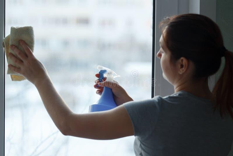 Het jonge meisje wast en maakt zorgvuldig een venster schoon royalty-vrije stock afbeelding