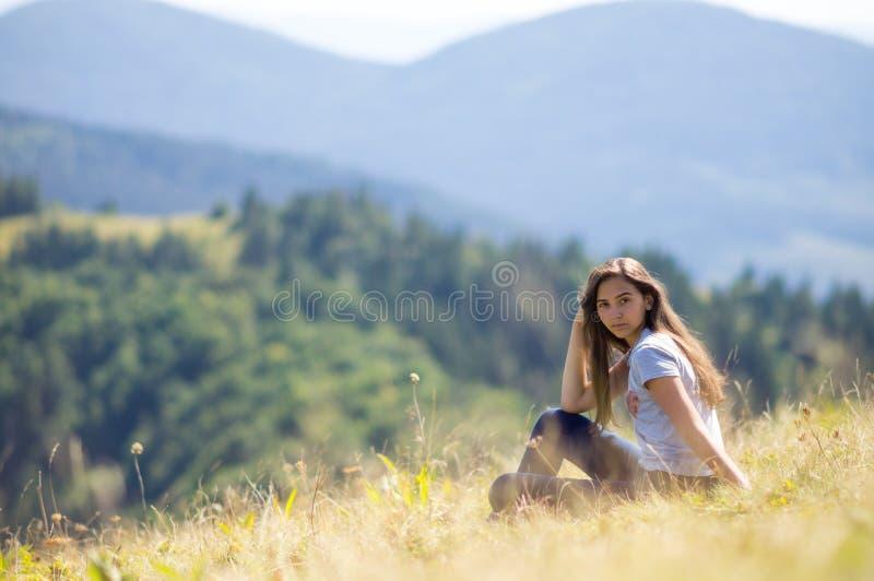Het jonge meisje zit op de berghelling royalty-vrije stock foto's