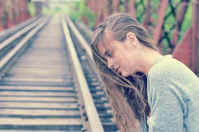 Het jonge meisje zit op de sporen voor treinen in profiel royalty-vrije stock foto