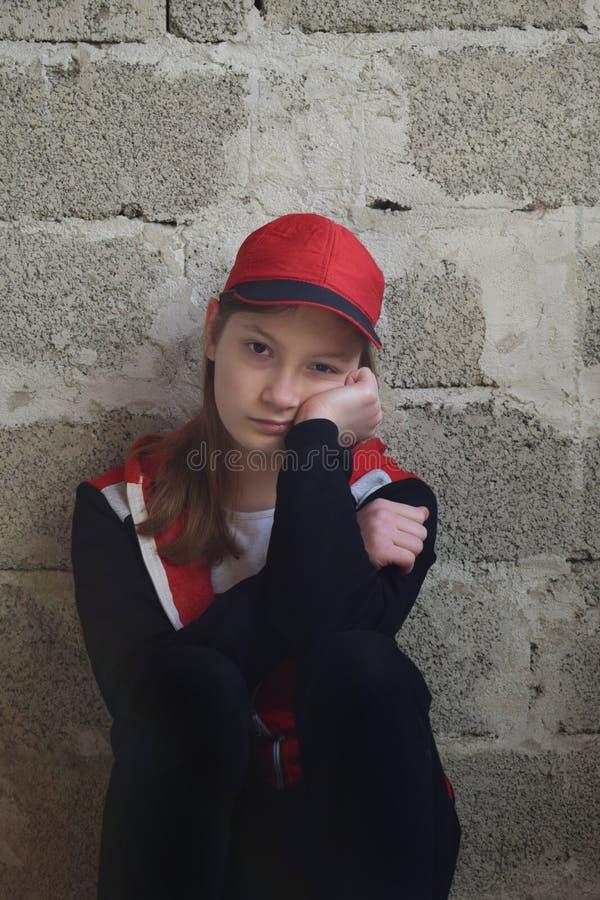 Het jonge meisje zit in zwart sportenkostuum, rood GLB Conceptenportret van een droevige tiener stock foto