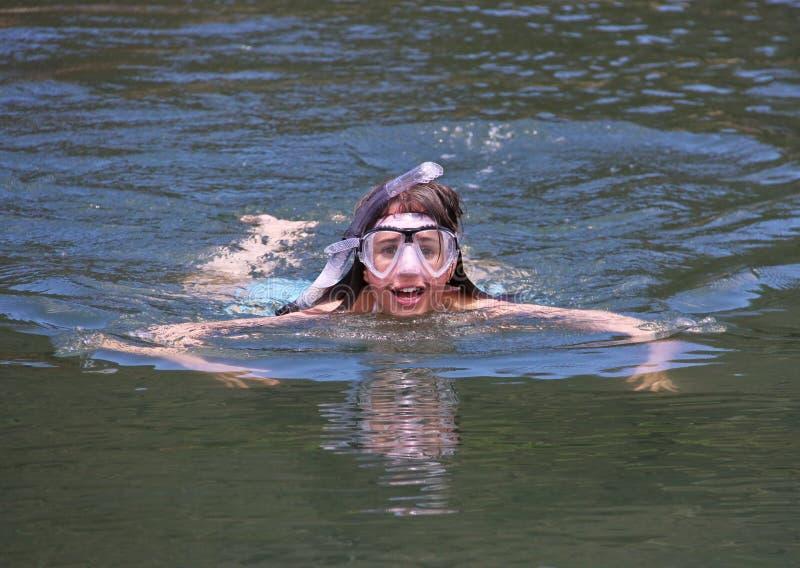 Het jonge meisje zwemmen met beschermende brillen en snorkelt stock afbeeldingen