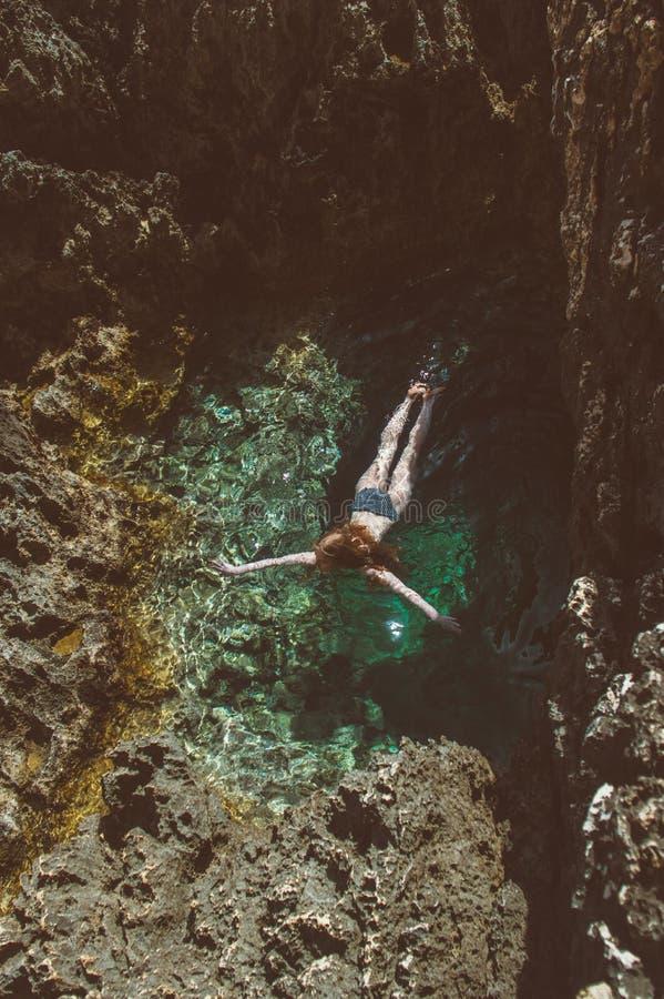 Het jonge meisje zwemt in de natuurlijke pool royalty-vrije stock afbeeldingen